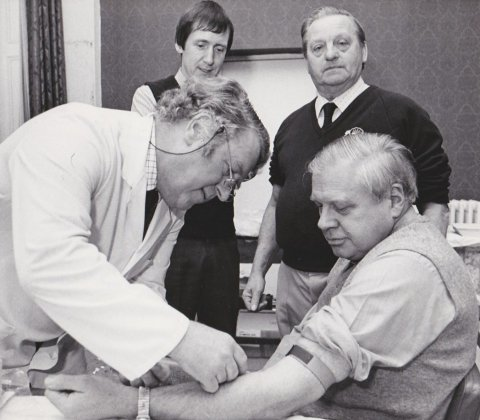 Dr Gill (rear left) observes as Dr Bell takes blood from FEPOW Bernard Sayles during a FEPOW meeting in Scarborough in 1979